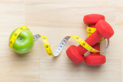 Concept of weight loss with fresh green apple, measuring tape and dumbbells. Fitness diet programme. Top view angle with copy spac Stock Image