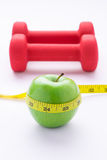 Concept of weight loss with fresh green apple, measuring tape and dumbbells. Fitness diet programme. Top view angle with copy spac Royalty Free Stock Photography