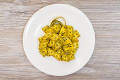 Concept of weightloss. Plate with yellow tape measure. Top view. Concept of weightloss dieting slimming healthy eating overweight. Top above overhead close up Royalty Free Stock Photo