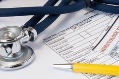 Concept werkplaats en primaire toelating van patiënt door algemene praktijkarts Stethoscoop, pen en resultaat van hematologieblo stock fotografie