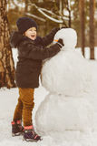 The concept of winter activities . Happy boy making snowman outdoor Stock Photos
