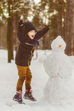 The concept of winter activities . Happy boy making snowman outdoor Royalty Free Stock Photography