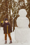 The concept of winter activities . Happy boy standing next to a snowman outdoor Stock Images