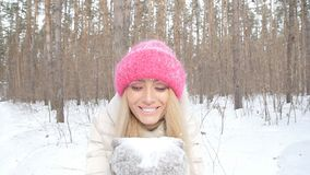 Concept of winter entertainment. Young woman having fun blowing fresh snow from her hands stock footage