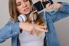 Concept of wireless headphones. Annoyed woman wants to cut the c stock photos
