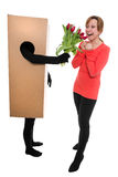 Concept: woman and package deliverer with flowers Royalty Free Stock Image