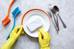 Concept of woman washing dishes on gray background top view royalty free stock photo