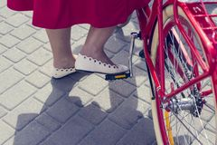 Concept: women on a bicycle. The girl in the red skirt puts his foot on the bicycle pedal. Part of the picture.  royalty free stock images