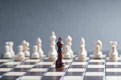 Concept of wooden chess. One black chess against white Royalty Free Stock Images