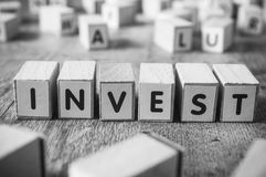 Concept word forming with cube - Invest. Concept word forming with cube on wooden desk background - Invest Stock Photography