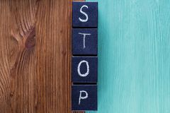 Concept of word Stop, contradistinction or versus. Word STOP on wooden cubes separates and contrasts the wooden background. Two-colored wooden background Royalty Free Stock Images