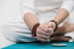 The concept of yoga and meditation. Close-up of the hands and feet of a man in white clothes on a light background. A royalty free stock images