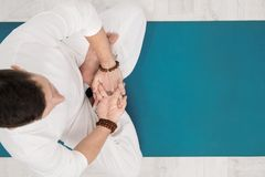 Concept of yoga and meditation. Close-up, hands of a man in white clothes, folded in prayer. White background and yellow royalty free stock photography