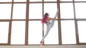 Concept zich het uitrekken en flexibiliteit Jonge vrouw in sportkleding die het uitrekken doen zich dichtbij venster in een wit b stock videobeelden