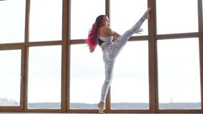 Concept zich het uitrekken en flexibiliteit Jonge vrouw in sportkleding die het uitrekken doen zich dichtbij venster in een wit b stock footage