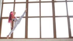 Concept zich het uitrekken en flexibiliteit Jonge vrouw in sportkleding die het uitrekken doen zich dichtbij venster in een wit b stock video