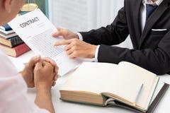 Concepten wet, Advocaat en zakenman die en bedrijfscontractdocumenten in bureau werken bespreken stock afbeelding
