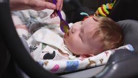 Conceptenbaby het voeden, kinderverzorging, eerste voedsel De moeder geeft het kind de eerste maaltijd met een lepel, die op ligt stock footage