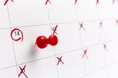 Conceptenbeeld van een kalender met rode duwspeld Close-up geschotene punaise in bijlage De vorm van het woordenhart op wit wordt Stock Fotografie