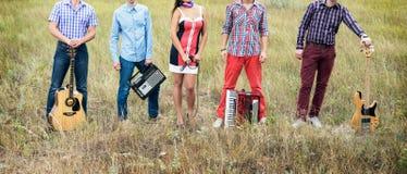 Conceptenfoto van muziekband met gitaren, microfoon en harmonika die zich in openlucht bevinden stock foto