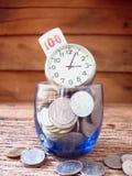 Conceptenidee, velen muntstuk in blauw glas met tijd, idee voor zaken Stock Afbeeldingen