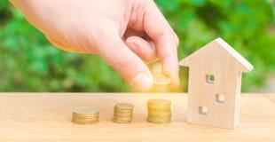 Concepteninvestering in onroerende goederen Besparingsgeld om een nieuw huis te kopen Blokhuis en stapels muntstukken van klein t royalty-vrije stock foto