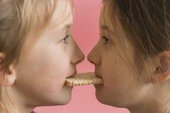 conceptenjonge geitjes die voor voedsel vechten de meisjes bijten één boterham Het concept van het voedseltekort stock foto