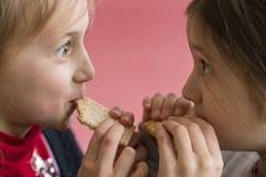 conceptenjonge geitjes die voor voedsel vechten de meisjes bijten ??n boterham Het concept van het voedseltekort stock fotografie