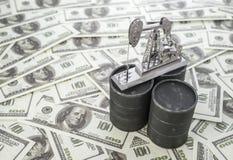 Conceptenvat en olie boorpomp op achtergrond van Amerikaanse dollarbankbiljet royalty-vrije stock afbeeldingen