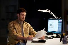 Concepteur avec des papiers fonctionnant au bureau de nuit photos stock