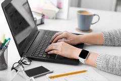 Concepteur avec la montre et l'ordinateur portable intelligents au bureau photographie stock
