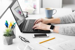 Concepteur avec la montre et l'ordinateur portable intelligents au bureau photo stock
