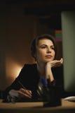 Concepteur concentré de jeune dame s'asseyant dans le bureau la nuit Image libre de droits
