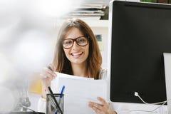 Concepteur créatif de jeune femme avec des documents fonctionnant dans le bureau. image libre de droits