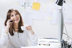 Concepteur créatif de jeune femme parlant avec le téléphone tout en buvant d'un café photos stock