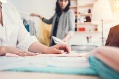 Concepteur d'habillement de deux jeunes travaillant dans le bureau de couture de conception La femme d'affaires cousent de nouvea photos stock
