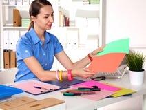 Concepteur de fille dans un bureau derrière une table Photos stock