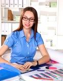 Concepteur de fille dans un bureau derrière une table Photo libre de droits