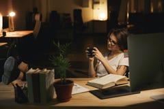 Concepteur de Madame s'asseyant à l'intérieur aux jeux de jeu de nuit par le téléphone Photos libres de droits