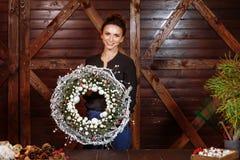 Concepteur de sourire mignon montrant à Noël la guirlande à feuilles persistantes d'arbre Jeune femme tenant la guirlande de Noël image stock