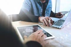 Concepteur de Web de deux collègues discutant les données et le comprimé numérique images stock