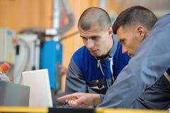 Concepteur deux en bois travaillant avec l'ordinateur portable dans l'atelier photo libre de droits