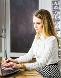 Concepteur féminin dans le bureau fonctionnant avec le comprimé graphique numérique et l'ordinateur portable Retoucher de photogr photos stock