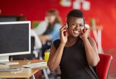 Concepteur féminin sûr écoutant la musique dans les bureaux créatifs rouges Images stock