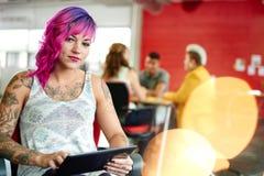 Concepteur féminin sûr et énervé travaillant à un comprimé numérique dans les bureaux créatifs rouges Image libre de droits
