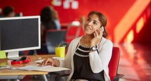 Concepteur féminin sûr parlant à un téléphone portable dans les bureaux créatifs rouges Images stock