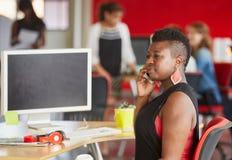 Concepteur féminin sûr parlant à un téléphone portable dans les bureaux créatifs rouges Photo stock