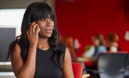 Concepteur féminin sûr parlant à un téléphone portable dans les bureaux créatifs rouges Image stock