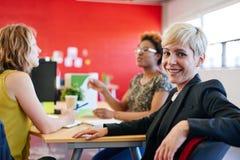 Concepteur féminin sûr s'asseyant à son bureau pour une séance de réflexion dans les bureaux créatifs rouges Photographie stock
