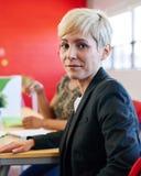 Concepteur féminin sûr s'asseyant à son bureau pour une séance de réflexion dans les bureaux créatifs rouges Images stock